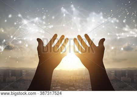 Technology Concept: Silhouette Many People Raised Hands Over City Sunset Background