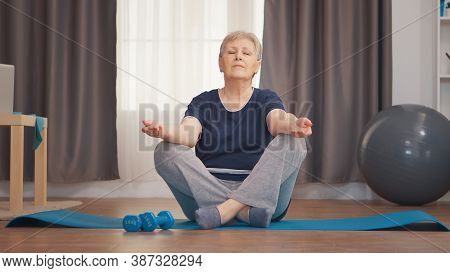 Peaceful Senior Woman With Eyes Closed Doing Yoga In Living Room. Active Healthy Lifestyle Sporty Ol