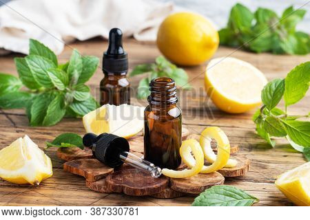 Lemon Citrus Fruit Essential Oil And Mint, Aromatherapy Oil Natural Organic Cosmetic On Rustic Wood