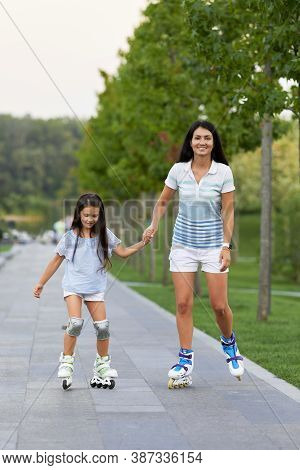 Young Mother And Her Little Daughter Rollerskating In Park In Sunny Day . Happy Family Have Fun