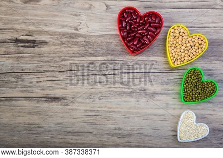 Red Beans In Red Heart Shaped Plastic Bowl. White Sesame Seeds In White Heart Shaped. Soybean In Yel