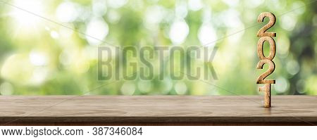 New Year 2021 Wood Number (3d Rendering) On Wooden Table At Blur Abstract Green Tree Bokeh Backgroun
