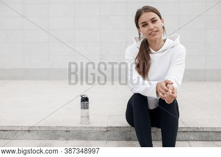 Portrait Of Fit And Sporty Young Woman Sitting With Botle Of Water Outdoor In The City