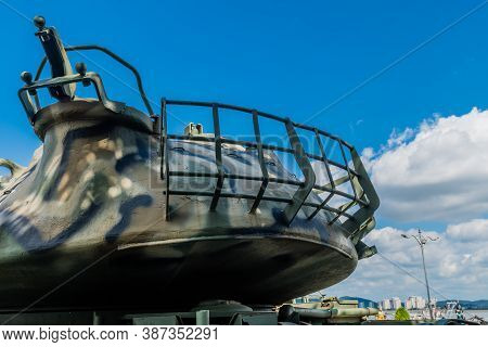 Rear View Of Gun Turret On Tank Displayed In Public Park Under Cloudy Sky.