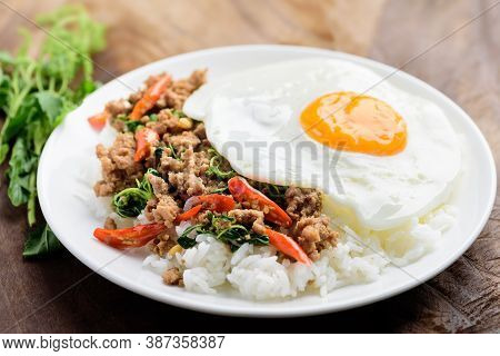 Thai Food, Stir-fried Holy Basil With Minced Pork And Fried Egg On Top Eating With Cooked Rice (pad