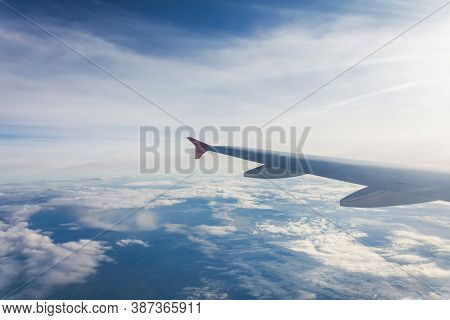 Wing Of An Airplane Flying Above The Clouds. Looks At The Sky From The Window Of The Plane, Using Ai