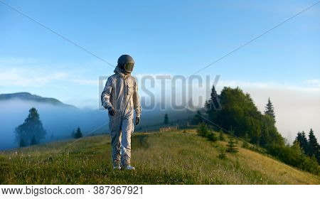 Cosmonaut Wearing White Space Suit And Helmet Walking Alone Sunny Green Mountain Glade In The Mornin