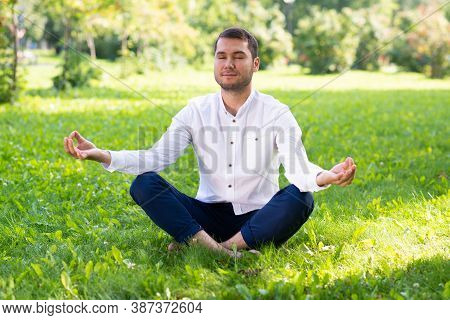 Young Man Meditates In Lotus Pose On Green Grass. Handsome Man In Casual Wear Practicing Of Yoga Wit
