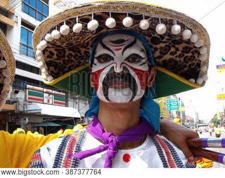 Bangkok, Thailand, November 14, 2015: A Man With A Large Hat And His Face Painted In Bright Colors I