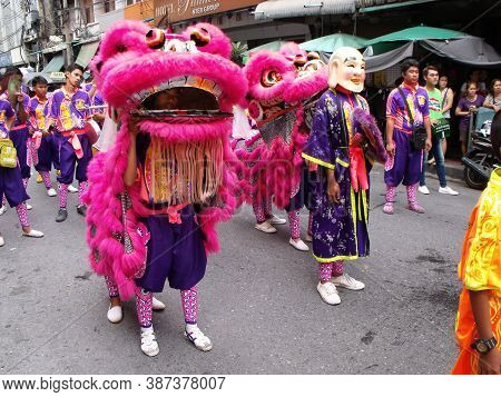 Bangkok, Thailand, November 14, 2015: A Man In Costume In Front Of Two Dancing Lions In The Parade O