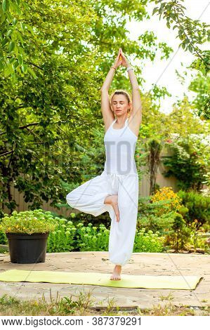 Young Woman Practices Yoga In The Summer Garden - Vrikshasana, Tree Pose.