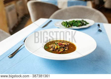 Spanish Traditional Oxtail Soup In White Plate On The Blue Table