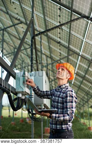 Operator In Helmet And With Laptop At Station Checking The Operation Of Solar Power Plant. Vertical
