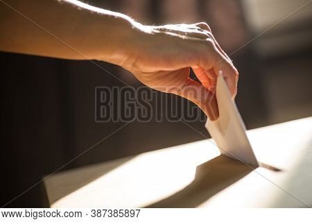 Conceptual Image Of A Person Voting, Casting A Ballot At A Polling Station, During Elections.