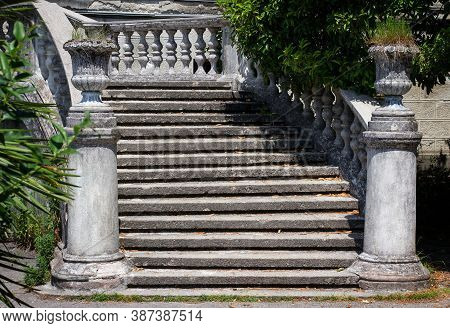 Old Stone Staircase In The Park. Ancient Staircase With Stone Balusters On A Background Of Green Veg