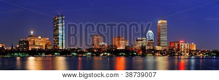 Boston city skyline with Prudential Tower and Hancock Building and urban skyscrapers over Charles River at dusk with lights and water reflection.