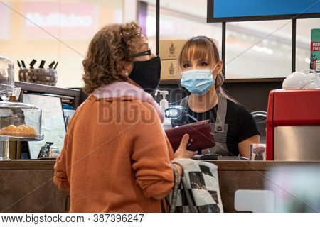 Vilnius, Lithuania - September 28 2020: Pretty Waitress With A Mask And Gloves Serving Client In A I