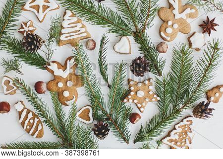 Christmas Gingerbread Cookies, Fir Branches And Pine Cones  On Wooden Background Flat Lay