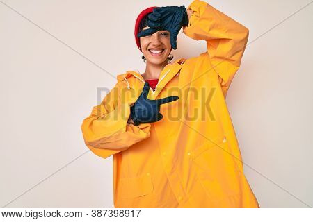 Beautiful brunettte woman wearing yellow raincoat smiling making frame with hands and fingers with happy face. creativity and photography concept.