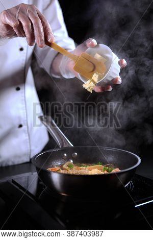 The Process Of Making Risotto. The Chef Prepares Risotto With Seafood. Unrecognizable Vertical Photo