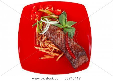 business lunch: served roasted beef meat steak on potatoes over red dish isolated over white