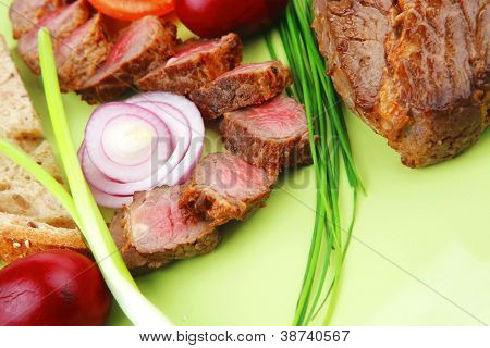 business lunch meat savory : roasted bbq meat served on green plate with tomatoes and sprouts isolated on white background