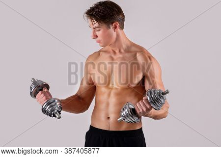 Strength Training Concept. Powerful Handsome Young Man With Bare Torso And Prominent Muscles Lifting
