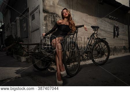 Urban portrait of gorgeous Young woman on vietnamese tricycle on the slum