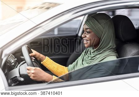 Cheerful African Muslim Lady In Headscarf Driving New Car In City, Riding Her New Vehicle, Got Drivi