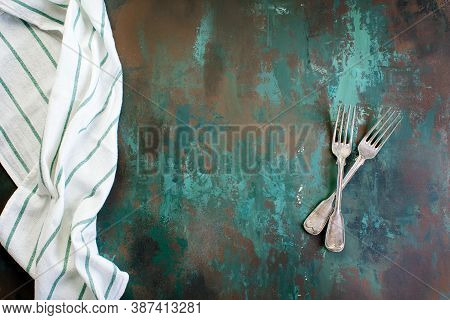Kitchen Background. Napkin And Fork With Knife On Rusty Grunge Background