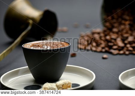 Traditional Turkish coffee served with Turkish delight over black background