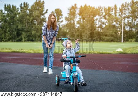 Little Boy Is Learning To Ride A Childrens Tricycle While Walking With His Mother. Concept Of Learni