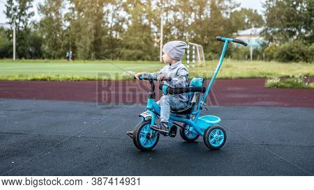 A Small Child Is Successfully Goes A Childrens Tricycle. Concept Of Learning To Ride A Bike And Spen