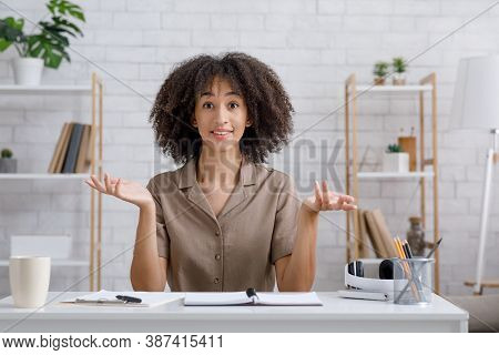 I Do Not Know Or Maybe. Attractive African American Female Spreads Her Arms To The Sides And Looks A
