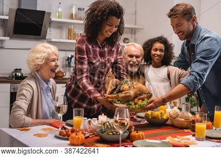 Focus Of Multiethnic Family Standing Near Turkey And Thanksgiving Dinner At Home