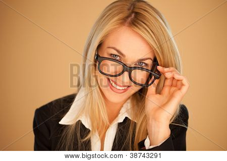 Attractive professional woman peering over the top of her glasses with a lovely smile