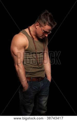 Dejected macho man in casual clothes and sunglasses with a well muscled physique standing despondently with his head down on a dark studio background