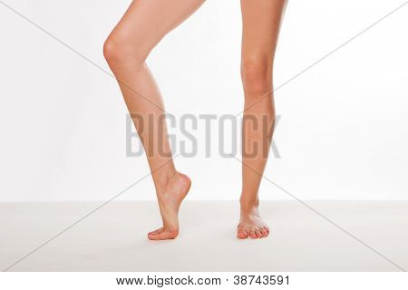 Pair of bare sexy womans legs with one foot raised up on tip toe and one flat on the ground on a white background