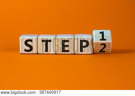 Step By Step. Turned A Cube And Changed The Expression 'step 1' To 'step 2'. Beautiful Orange Backgr