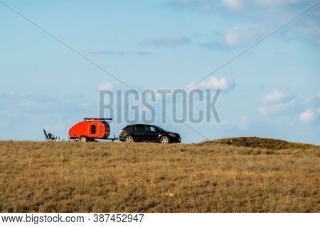 A Lone Red Trailer Is Located In The Middle Of A Sun-baked Steppe. There Is A Table And Chairs Near