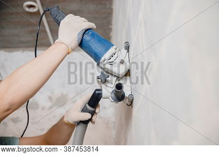 Builder Worker Cutting Electrical Chase In Concrete Wall With Circulation Saw Drill Diamond Crown