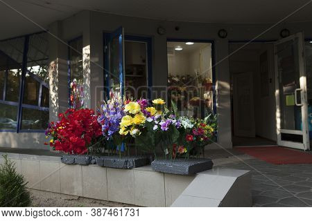 Shop Selling Artificial Flowers. Multicolored Non-natural Flowers Near The Flower Shop.