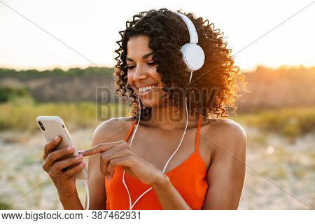 Image of cheerful young african woman using mobile phone while listening music with headphones at the beach outside