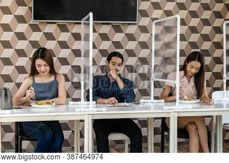 Restaurant customers have a seat with table shield partition for social distancing to reduce infection of coronavirus covid-19 pandemic. Restaurant new normal lifestyle.