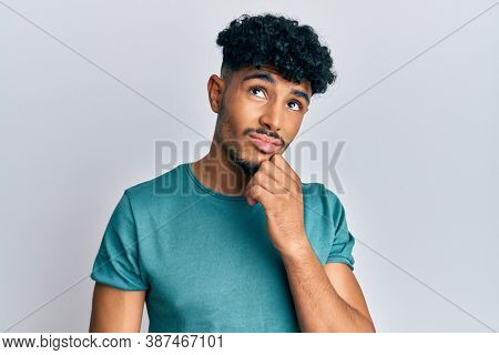 Young arab handsome man wearing casual clothes serious face thinking about question with hand on chin, thoughtful about confusing idea