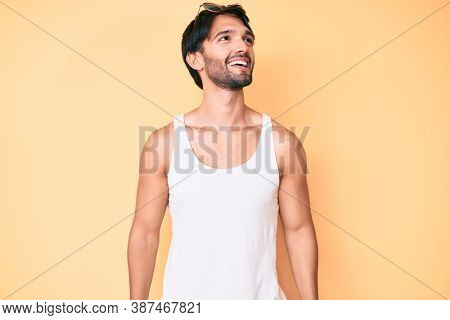 Handsome hispanic man wearing summer look and sunglasses looking away to side with smile on face, natural expression. laughing confident.