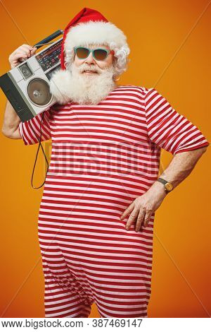 Cool DJ Santa Claus in sunglasses holds tape recorder on a festive background with lights. Christmas songs and music. New Year party.