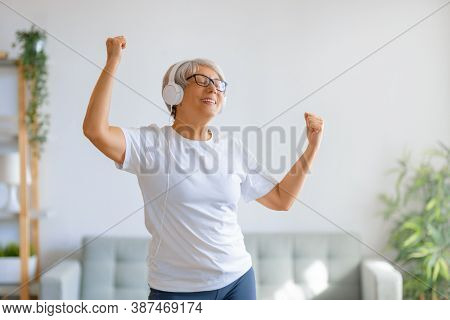 Cheerful senior woman listening to music in headphones and dancing in the room at home.