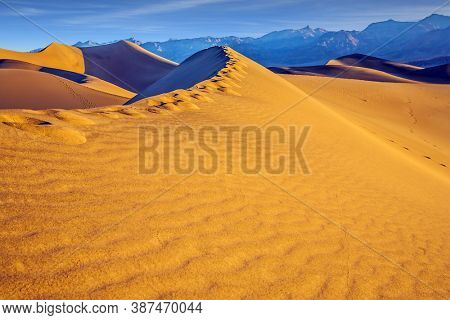Mesquite Flat Sand Dunes - dunes in Death Valley. Human footprints visible along the crest of the dune. The morning. The sand lies in light waves. The concept of extreme and photo tourism