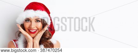 Portrait of beautiful woman in santa hat with surprised face, white background with copy space